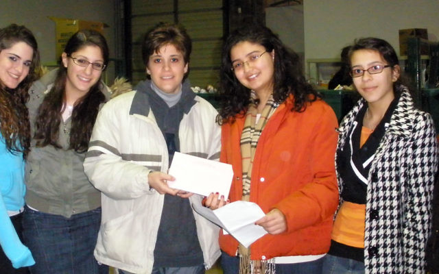 Miryam Brami, a Moshe Aaron Yeshiva High School senior from Highland Park, presents a check on behalf of the Jewish Federation of Greater Middlesex County to Jennifer Apostol, coordinator of Middlesex County's emergency food network. Joining her are