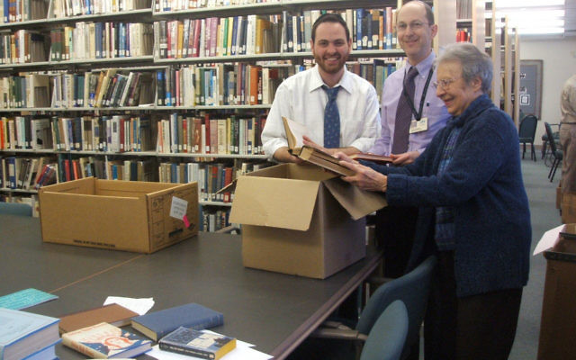 Looking over surplus books at the Waldor Memorial Library in Whippany are, from left, Rabbi Yossi Sirote, executive director of Abraham's Tent in Highland Park; Arthur Sandman, associate executive vice president of United Jewish Communities of Metro