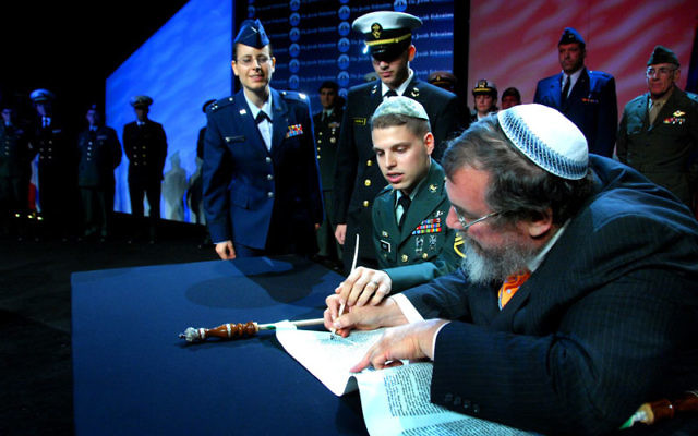 Scribe Zerach Greenfield writes part of a Torah scroll in November during the Jewish Federations of North America General Assembly; the scroll will be sent to American soldiers overseas. Photo by Robert A. Cumins