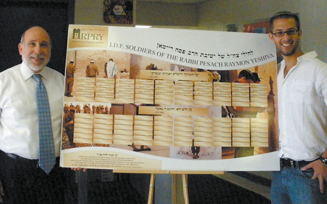 Rabbi Shraga Gross, principal of Rabbi Pesach Raymon Yeshiva in Edison, and RPRY alumnus Avi Sholom stand by an architectural drawing of the Wall of Honor to be erected at the Edison school listing its more than 30 grads who have served in the IDF. Shol