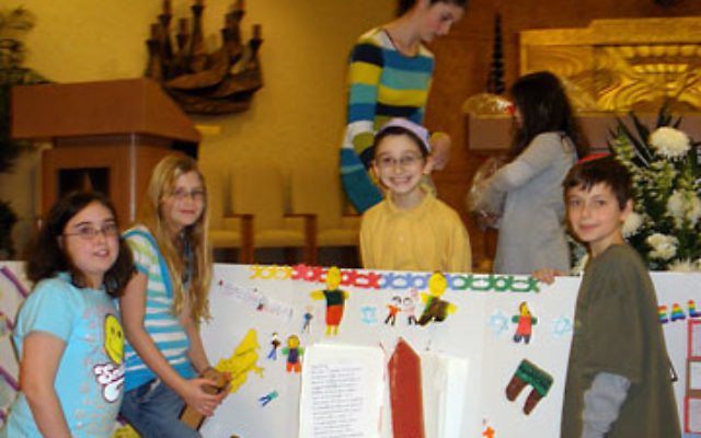 Showing a poster highlighting the federation's support for programs strengthening Jewish identity among kindergartners in Russia are fifth-graders, from left, Aviva Kamens of Highland Park, Gabrielle Hartman of Hillsborough, and Joel Herniter and Jo