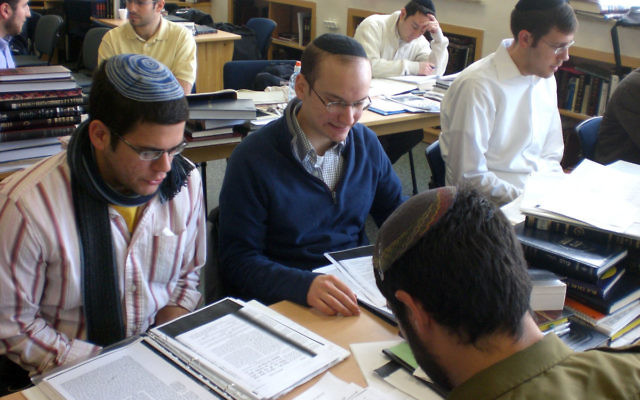 Ari Neuman, left, learns with Israel Defense Force soldiers and fellow students at Yeshiva University's Gruss campus in Jerusalem.