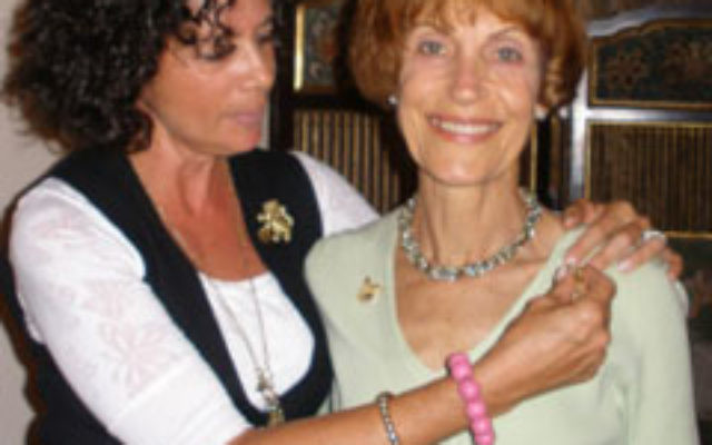Gail Shapiro-Scott, right, receives her Lion of Judah pin from event cochair Arlene Frumkin.