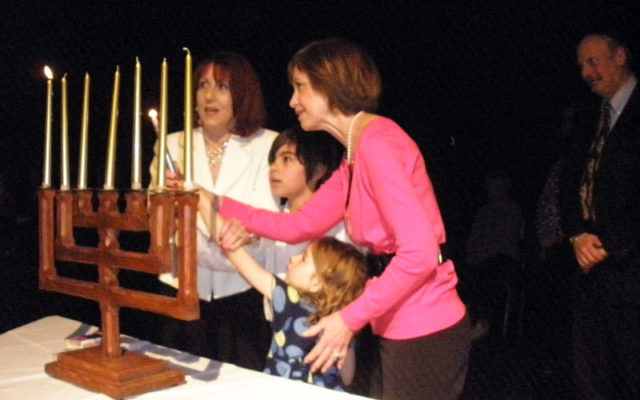 Ricklis committee member Rochelle Grossman, left, and Linda Kamins, both children of Holocaust survivors, light a candle in remembrance. They are joined by Grossman's grandchildren, Nathan and Samantha. Photos by Debra Rubin