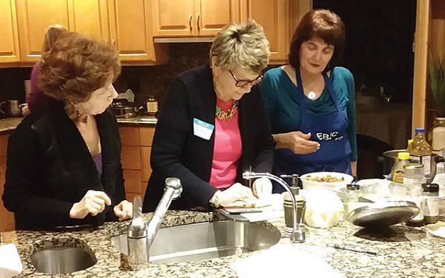 Yvette Schlussel, right, guides Beth Hoffman on the proper technique for making healthy quinoa-filled stuffed cabbage as Vera Galleid looks on at a recent Hadassah cooking demonstration.