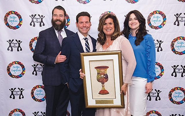 Drs. Mindy and David Estin, center, accept their Hand in Hand award from Rabbi Laibel and Chani Schapiro.