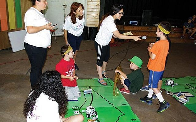 Youngsters at NJY Camps learn how to maneuver their robot cars on the map of Israel — as they answer questions about the country in order to proceed — with, from left, Shahaf Pinion, robotics teacher from ORT Kadima Mada in Dimona; Ayelet Abramovitch, chief of informal education at ORT Kadima Mada; and Ziv Itzhak and, in foreground, Ta'ir David, both from ORT Kadima Mada in Dimona.