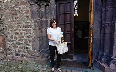 Joan Herz Kamens at the entrance of the Rashi Synagogue in Worms, Germany, holding photos her parents had taken at the same spot. Photos courtesy Kamens family