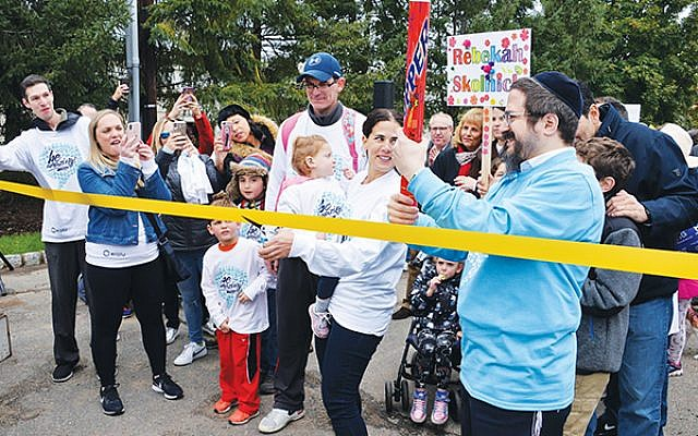 Beth Skolnick, center, looks at Friendship Circle CEO Rabbi Zalman Grossbaum, at right, as she cuts the ribbon to start the annual Friendship Circle Walk on Sunday, Oct. 28.  Photos by Jerry Siskind
