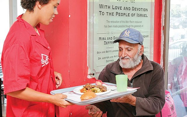 A diner being served at Meir Panim's soup kitchen.