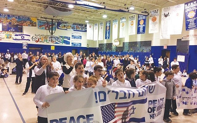 Students at Rabbi Pesach Raymon Yeshiva in Edison welcome members of a unit of IDF soldiers in the community for the Peace of Mind program. Photo courtesy Leslie Ostrin