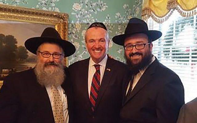 Gov. Phil Murphy is flanked by Rabbi Yosef Carlebach, left, and Rabbi Mendy  Carlebach.