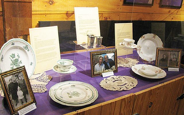 Display case with dishes owned by Lola Kline, whose Holocaust survivor parents brought them to the United States; Kiddush cups passed down for five generations in the Helfand family; and the Limoges china given to Alice Berman's grandparents for their 1902 wedding. (Photo courtesy Jewish Heritage Museum of Monmouth County)