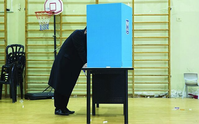 A charedi Orthodox man stands behind a voting booth before casting his ballot Tuesday in Israel's general elections in Bnei Brak. Getty Images