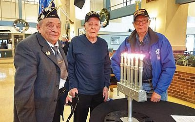 Three World War II veterans — from left, Bernard Rothenberg of Manalapan; Robert Duffy, formerly of Rockaway and now a resident of the Menlo Park Veterans Memorial Home; and Leo Rosenzweig of Manalapan — lit memorial candles for Holocaust victims during the Yom HaShoah ceremony. Photo by Debra Rubin