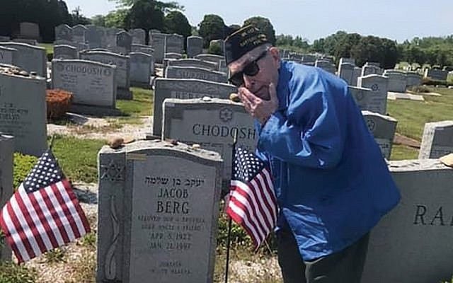 During a previous Memorial Day weekend, Louis Raiman places flags on the grave of Jewish war veteran Jacob Berg at Mount Lebanon Cemetery in Woodbridge.  Photo courtesy Sonja Erdelyi