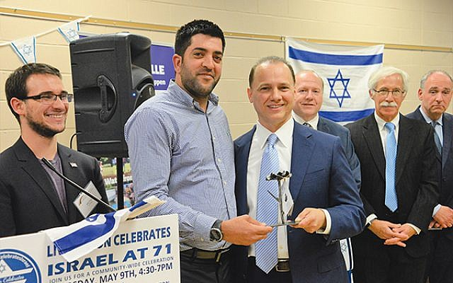 Naor Rohaker, second from left, the deputy mayor of Livingston's sister city, Ofakim, Israel, presents Livingston Mayor Al Anthony, third from left, with a sculpture of a flower made from a Gazan rocket that hit southern Israel. Photos by Jerry Siskind