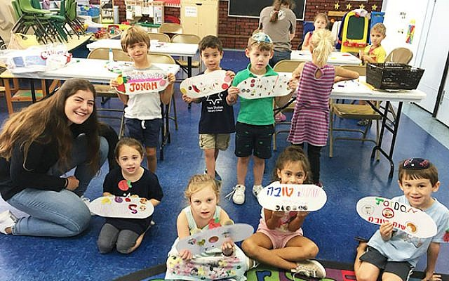 Students from Congregation Neve Shalom in Metuchen are helped with a craft project by Israeli Shinshin Maya Shany. Photo courtesy Jewish Federation in the Heart of NJ