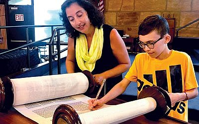 Rabbi Rebecca Gutterman assists Tyler Nemiroff with his Torah reading in preparation for his bar mitzvah at Temple Emanu-El in Edison. Photo courtesy Temple Emanu-El