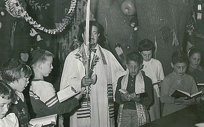 Rabbi Joseph Gelberman — the Jewish Center's first full-time religious leader — who was hired in 1955, leads a service for youngsters in the sukkah in 1958.  Photos courtesy The Jewish Center