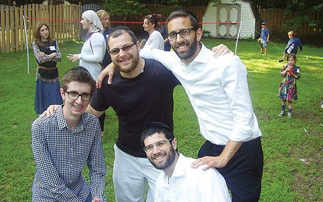 An MJC barbecue in July was attended by, from left, Adam Ilhaber, Steve Tzerlin, and Rabbi Avi Kramer. Kneeling in front is MJC co-director Rabbi Shalom Jacoby. Photos courtesy Manalapan Jewish Connection