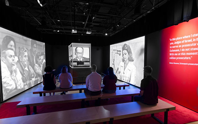 Eichmann's glass booth is surrounded by images of his trial, part of which can be seen on a video.