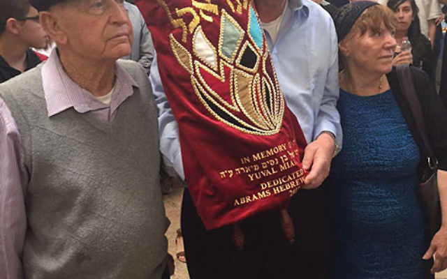 Rabbi Ira Budow, director of Abrams Hebrew Academy, is flanked by Nissim and Susan Miara, parents of Yuval, at the Torah dedication ceremony in Jerusalem.