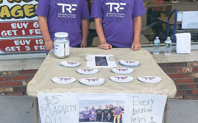 Geoffrey and his friend Hannah Zwim sell TRF logo car magnets outside a local business.