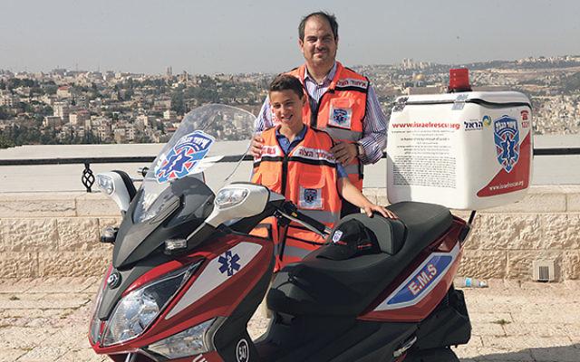 Jared Gehn with United Hatzalah president Eli Beer and the ambucycle he dedicated.