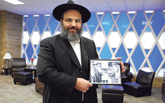Rabbi Moshe Hezrony holds up a photo of synagogue leaders taken in the mid-1950s, around the time ground was broken for the Congregation Anshei Roosevelt building.