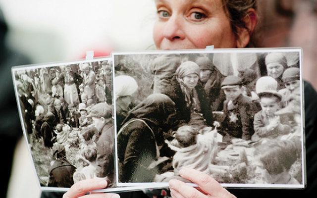 Joanie Schwarz holding up her photographs of Holocaust survivors.