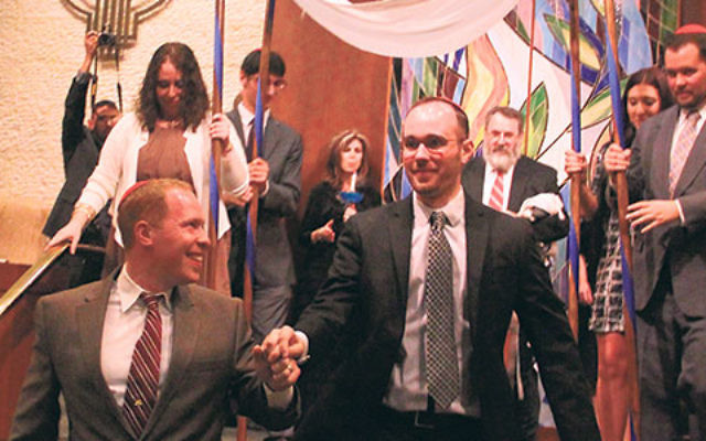 """BJ, left, and Duncan Solomon celebrate their """"upgrade"""" to full marital status at Congregation Beth Israel, with a ceremony conducted by Rabbi George Nudell (behind Duncan)."""