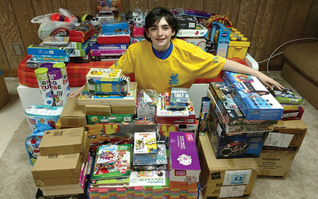 Tyler Levy with some of the 200 toys and games he has collected for children diagnosed with cancer. Photo by Scott Levy