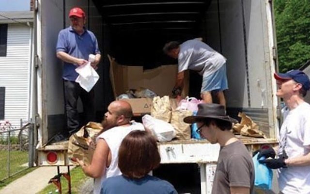 Rabbi Steven Bayar, left, and volunteers from B'nai Israel in Millburn help unload a 53-foot food truck with donated canned goods and other foodstuffs for the residents of McRoberts, Ky. Photo Courtesy Glenn Rosenkrantz