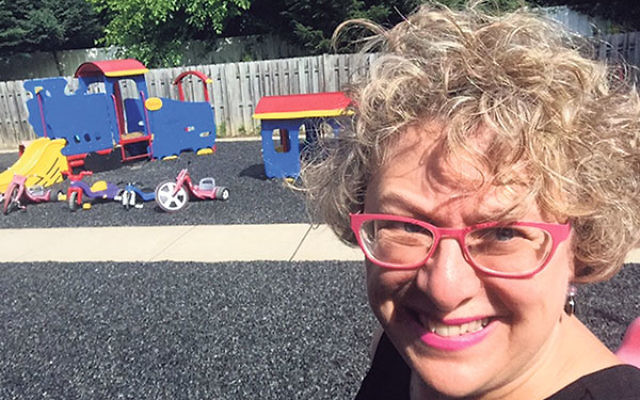 "Anne Berman-Waldorf, director of lifelong education at Congregation Beth Chaim, in front of the preschool's playground. ""We see the potential in every child,"" she said."
