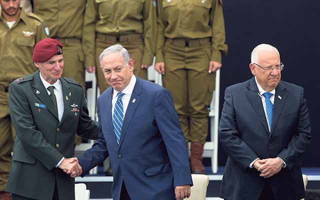 Prime Minister Benjamin Netanyahu, center, shaking hands with Deputy IDF Chief of Staff Yair Golan, and standing with President Reuven Rivlin, at an Israeli Independence Day ceremony honoring soldiers, May 12.
