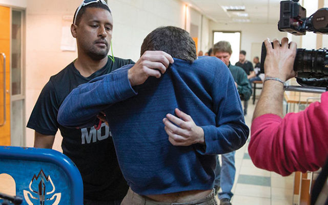 The JCC bomb threat suspect, Michael Kaydar, leaves court in Rishon Lezion, Israel, on March 23. Jack Guez/AFP/Getty Images via JTA