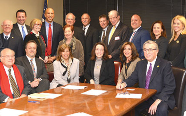 Meeting with Sen. Cory Booker, standing, fifth from left, are State Association board members and federation leaders, from left, front row, Roger Jacobs (Jewish Federation of Greater MetroWest NJ); Eric Lavitsky (Jewish Federation of Somerset Hunterdon Wa