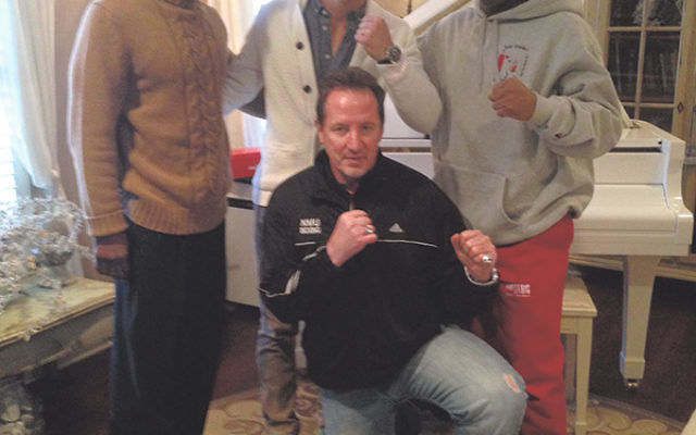Dustin Fleischer, standing, center, with his father, Phil, kneeling; his trainer, Jamal Abdullah, left; and his martial arts instructor, John Gaddy.