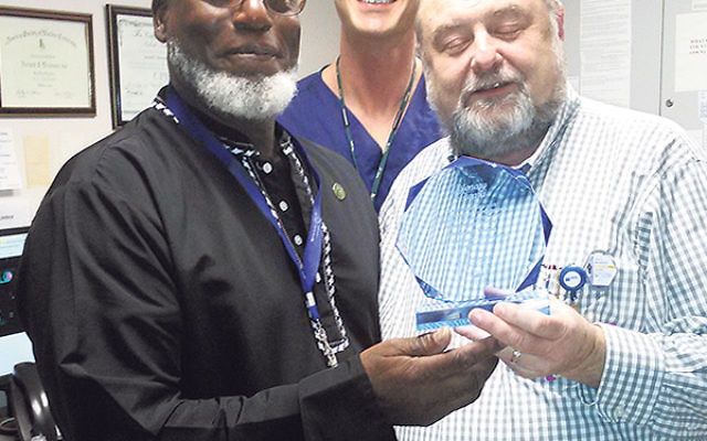 """Imam Zulqarnain Abdu-Shahid, Muslim chaplain at Staten Island University Hospital, presents Dr. Arnold Brenner with the Visionary Award for """"leading-edge spirit and creative approach to every pursuit."""""""