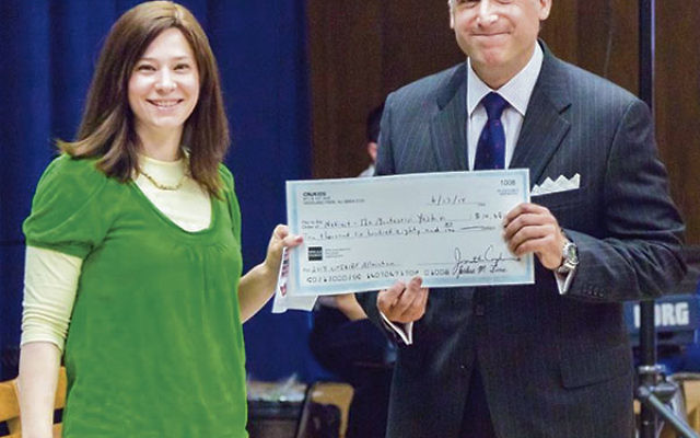 Michelle Klein Pincus, a cnjKids board member, presents a check to Netivot board president Jeffrey Schreiber to be used to give parents a credit on their tuition.