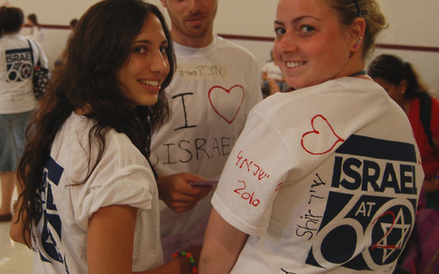 Israeli counselors, from left, Shani Bitkover, Izik Daniel, and Shir Altshuler show off their T-shirt allegiance to Israel at the Y's Israel Day event.