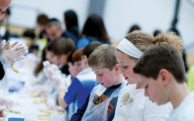 Students learn how to braid the dough.