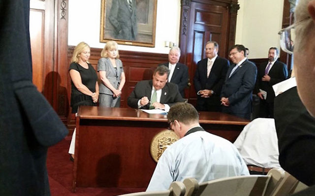 NJ Gov. Chris Christie, at a State House ceremony in Trenton, signing a bill prohibiting the state's pension and annuity funds from investing in companies that boycott Israel or Israeli businesses, Aug. 16, 2016. (Josh Pruzansky)