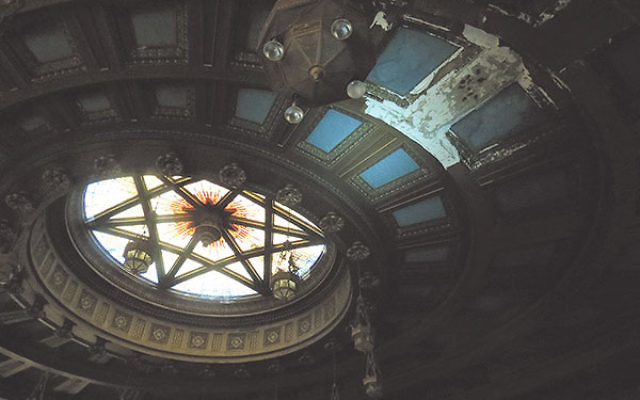 A large patch of plaster is missing from the sanctuary ceiling a few feet from the stained-glass star of David on its dome.