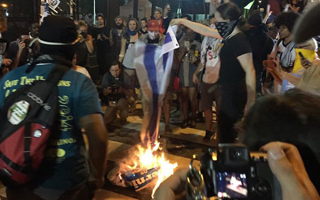 Protestors burning an Israeli flag outside the Democratic convention in Philadelphia, July 26, 2016. (Screenshot from Twitter)