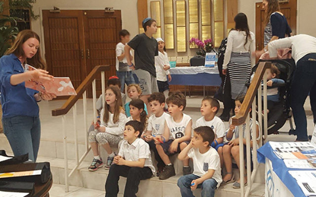 Lior Ben-Zvi reads to youngsters as part of the children's program. Photo COURTESY Jewish Federation in the Heart of NJ