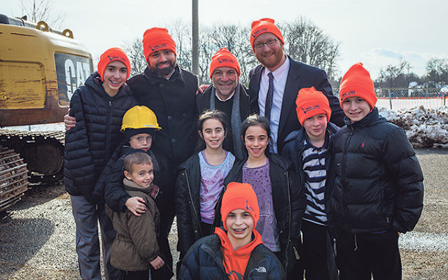 At the demolition site, Torah Links of Middlesex County president Dr. Steve Reich, center, and codirectors Rabbis Shlomo Landau, left, and Dovid Gross are joined in celebration by young people, many wearing the orange ski caps given out by the organizatio
