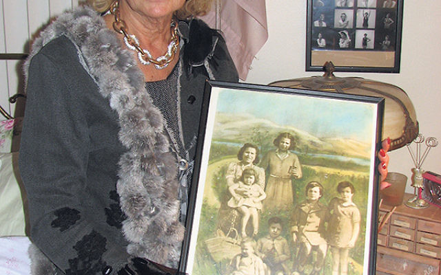 Paulette Dorflaufer in her Livingston home, holding a photo of herself as an infant, her mother, and four siblings. The siblings and her mother were murdered in Auschwitz.