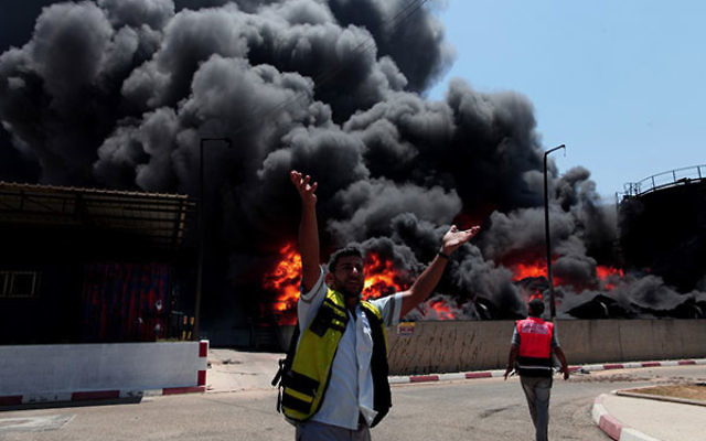 Palestinian men seen in front of a fire raging at the Gaza's main power plant following an overnight Israeli airstrike, south of Gaza City, July 29.